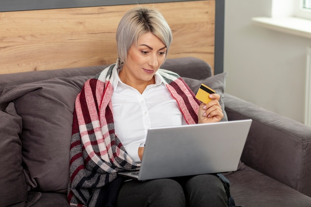 Mulher no escritório com laptop e cartão de crédito Foto gratuita