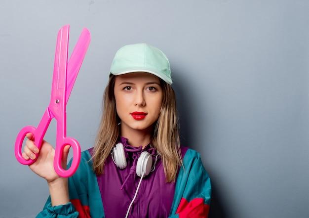 Mulher no estilo de roupa dos anos 90 com grandes tesouras Foto Premium