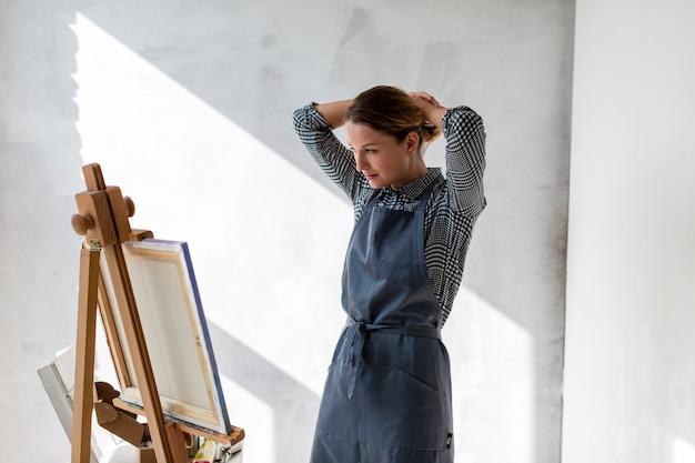 Mulher no estúdio com lona e cavalete Foto gratuita