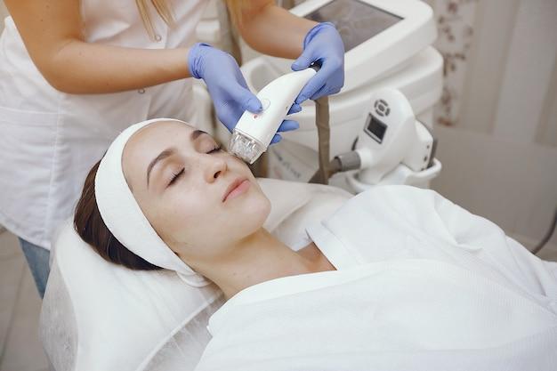 Mulher no estúdio de cosmetologia na depilação a laser Foto gratuita