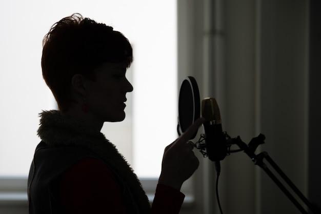 Mulher no estúdio de gravação gravando cantando e falando para processar e usar para filme e vídeo Foto Premium