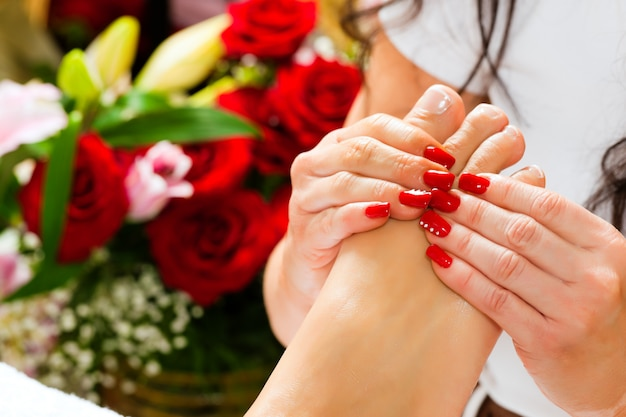 Mulher no estúdio de unhas recebendo massagem nos pés Foto Premium