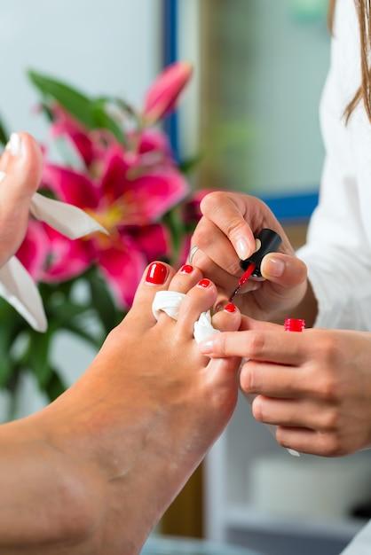 Mulher no estúdio de unhas recebendo pedicure Foto Premium