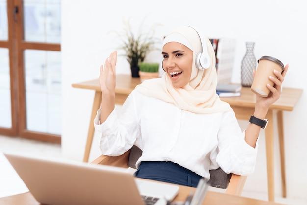 Mulher no hijab ouve música em fones de ouvido Foto Premium