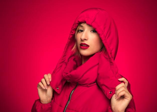 Mulher no inverno vermelho casaco com capuz fundo roxo Foto gratuita