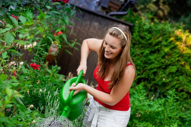 Mulher no jardim a regar flores Foto Premium