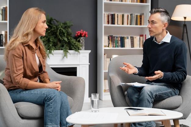 Mulher no meio do tiro falando com o conselheiro masculino Foto gratuita