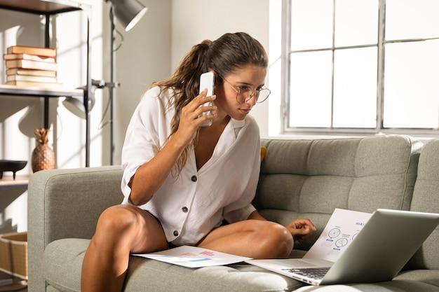 Mulher no meio do tiro no sofá falando ao telefone Foto gratuita