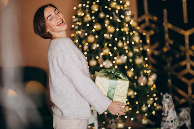Mulher no natal, segurando um presente de natal pela árvore de natal Foto gratuita