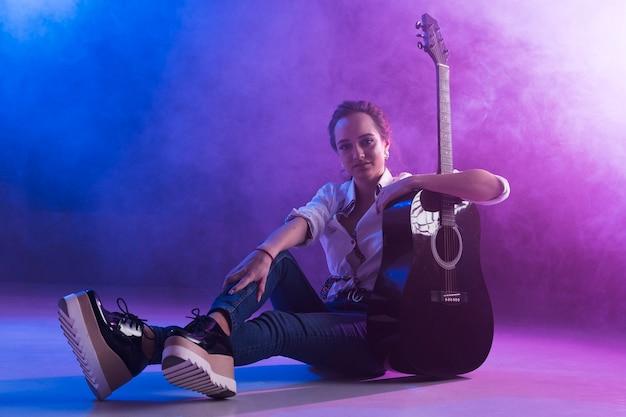 Mulher no palco com violão Foto gratuita