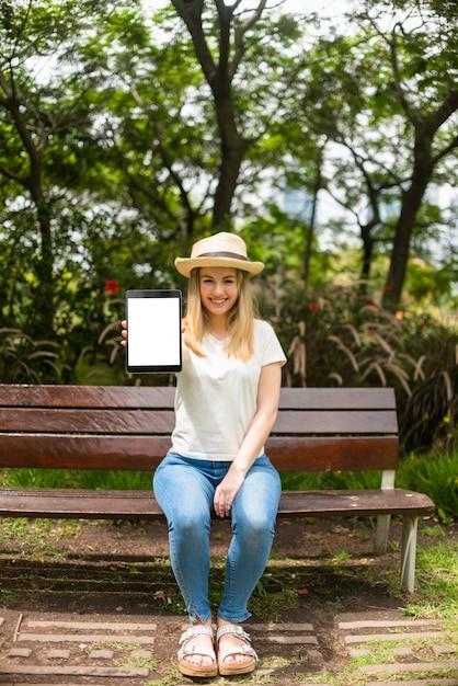 Mulher no parque mostrando tablet com tela em branco Foto gratuita