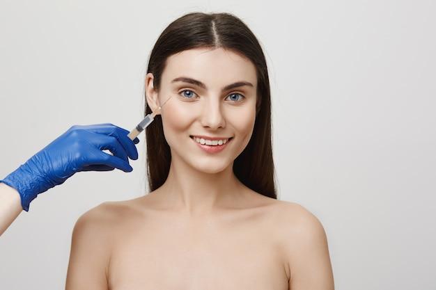 Mulher no salão de beleza sorrindo alegre, recebe injeção facial de bottox com seringa Foto gratuita