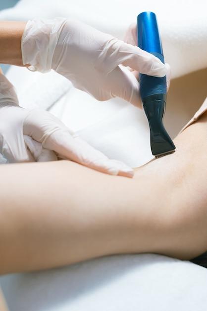 Mulher no salão fazendo procedimento de depilação nas axilas Foto Premium
