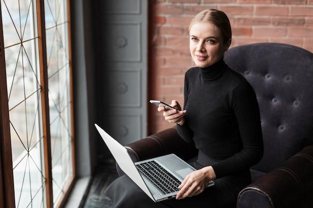 Mulher no sofá com o laptop e celular Foto gratuita