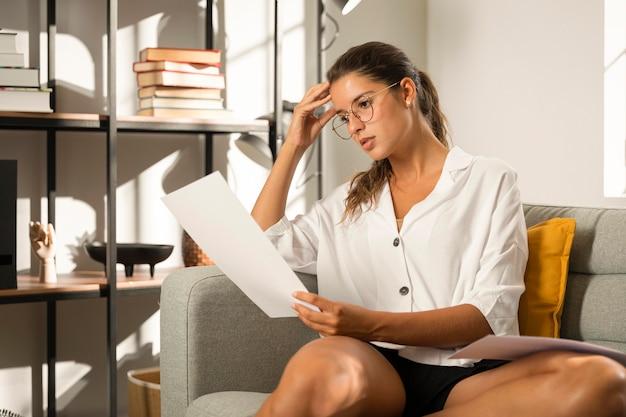 Mulher no sofá olhando para o papel Foto gratuita