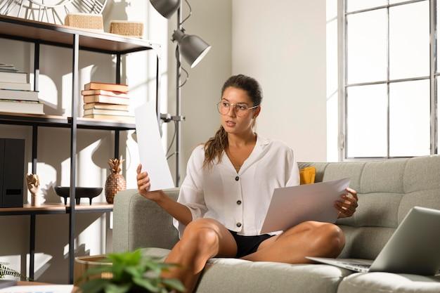 Mulher no sofá segurando papéis Foto gratuita