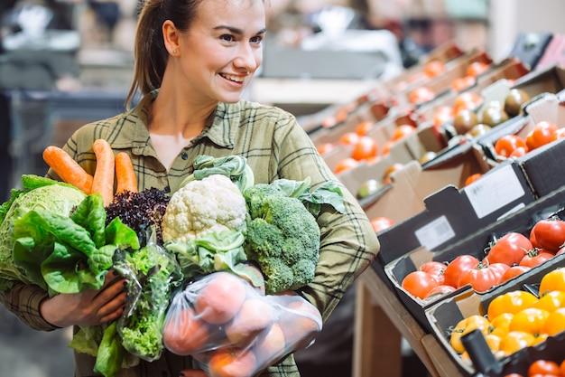 Mulher no supermercado. mulher jovem e bonita às compras em um supermercado e comprar legumes orgânicos frescos Foto gratuita