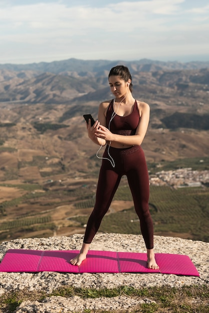 Mulher no tapete de ioga, verificando o telefone Foto gratuita