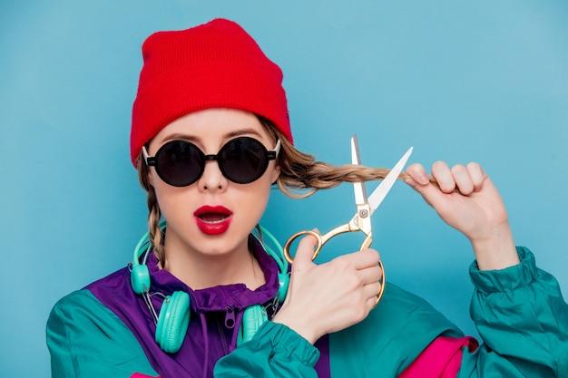 Mulher no terno dos anos 90 com fones de ouvido e tesoura Foto Premium