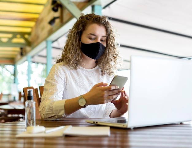 Mulher no terraço com máscara usando telefone Foto gratuita
