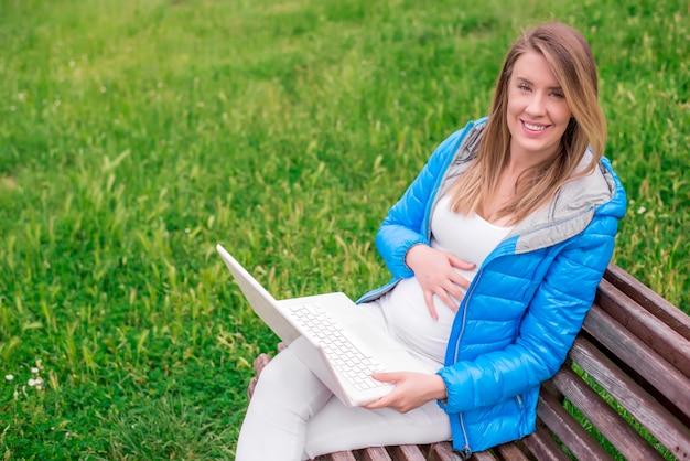 Mulher nova atraente com sorriso toothy usando o laptop ao ar livre Foto gratuita