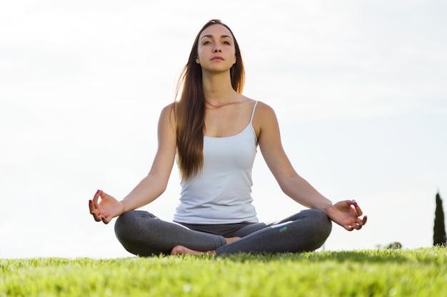 Mulher nova bonita que faz a ioga na rua. Foto gratuita