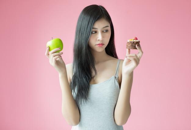 Mulher nova bonita que faz uma escolha entre um bolo e uma maçã Foto gratuita