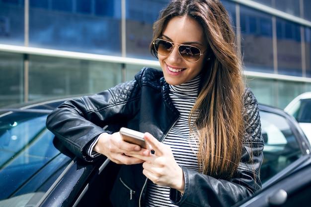 Mulher nova bonita que usa seu telefone móvel no carro. Foto gratuita