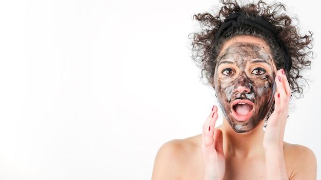 Mulher nova chocada com máscara de cara preta sobre sua face isolada no fundo branco Foto gratuita