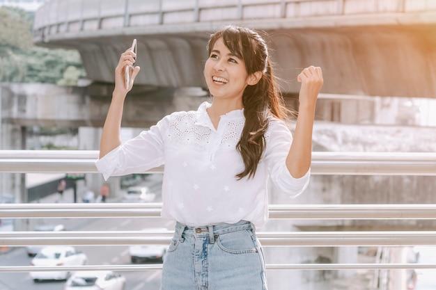 Mulher nova com mãos levantadas que shouting e que cheering na cidade ao ar livre. Foto Premium