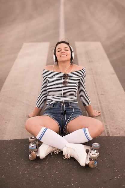 Mulher nova de sorriso que desgasta o patim de rolo que senta-se na música de escuta da estrada no auscultadores Foto gratuita