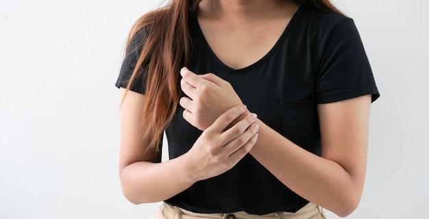 Mulher nova do escritório que sofre da dor da mão no fundo branco. Foto Premium