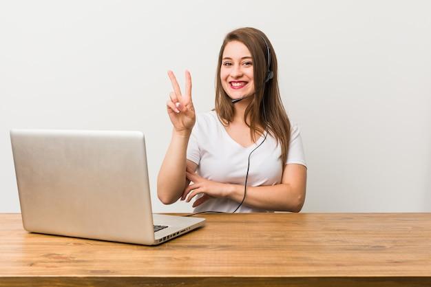 Mulher nova do telemarketer que mostra o número dois com dedos. Foto Premium