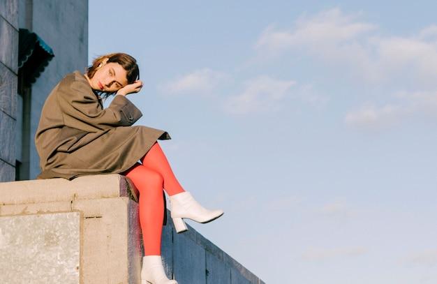 Mulher nova entediada contemplada que senta-se na parede contra o azul manhoso Foto gratuita