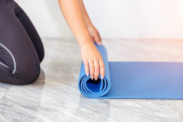 Mulher nova que dobra a esteira azul da ioga ou da aptidão após elaborar em casa Foto Premium