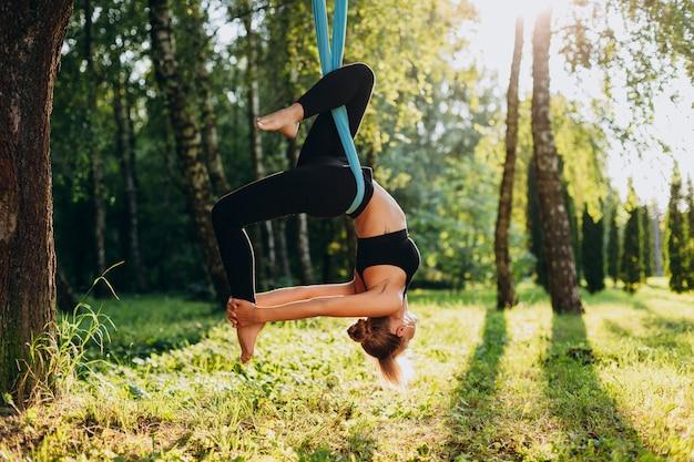 Mulher nova que faz a ioga da mosca no cair da árvore de cabeça para baixo. Foto Premium