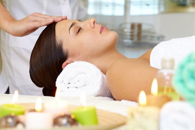 Mulher nova que recebe a massagem facial Foto gratuita