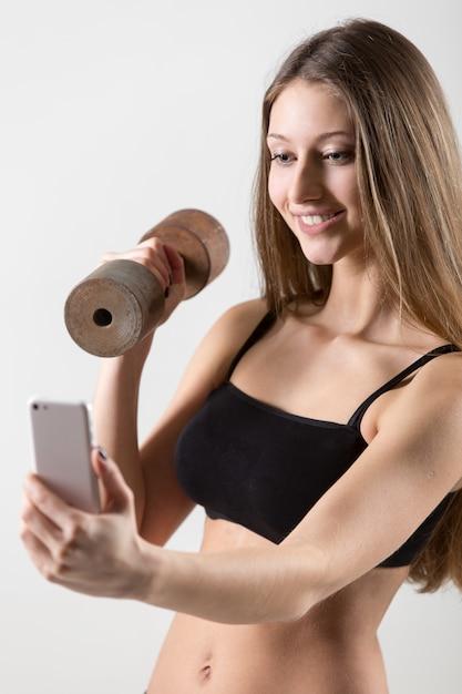 Mulher nova que toma uma foto, segurando um haltere Foto gratuita