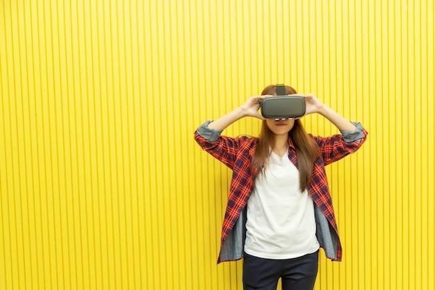 Mulher nova que usa o jogo da cabeça de vr para ver os filmes 3d. tecnologia moderna para casa entertainme Foto Premium