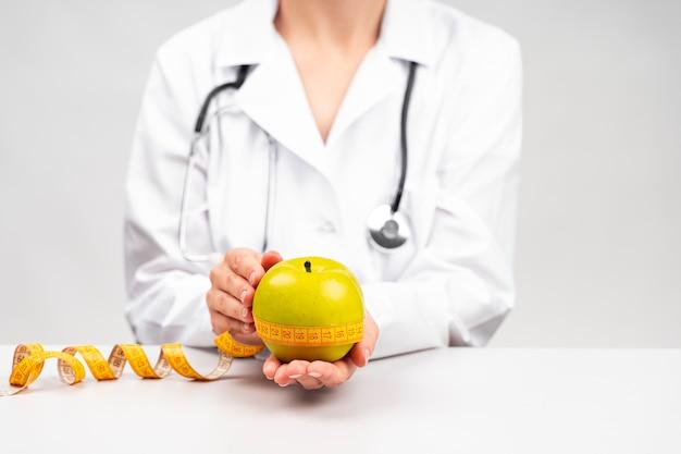 Mulher nutricionista segurando uma maçã Foto gratuita
