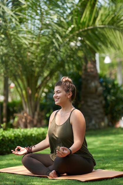Mulher obesa praticando ioga Foto gratuita