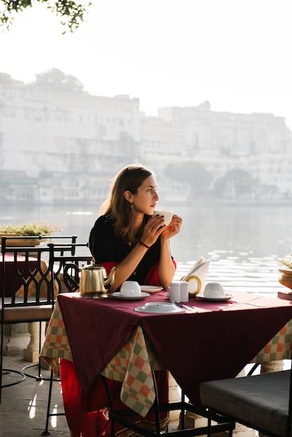 Mulher ocidental, tendo, um, teatime, em, um, café, em, udaipur Foto gratuita