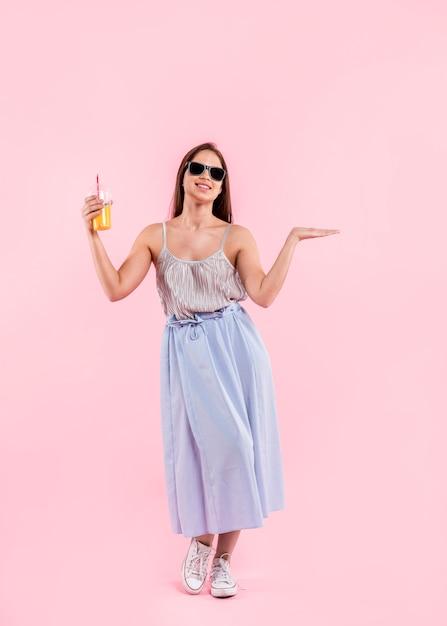 Mulher, óculos de sol, ficar, segurando, vidro, suco Foto gratuita