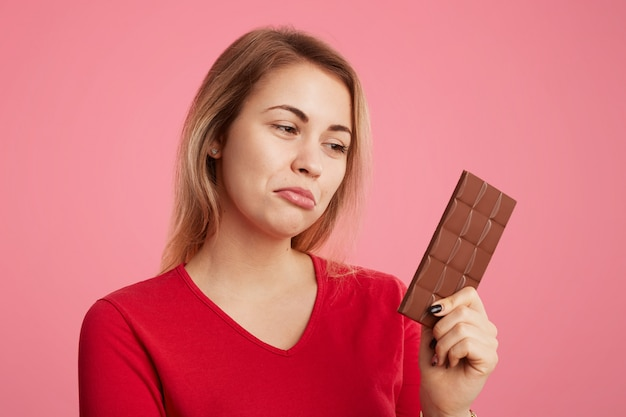 Mulher olha com expressão descontente para barra de chocolate doce, mantém a dieta, não pode comê-lo para ser magro e desportivo Foto gratuita