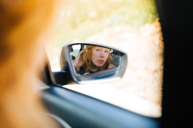 Mulher olha, em, vista dianteira, espelho, carro Foto gratuita