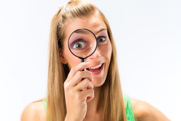 Mulher olhando através de lupa ou lupa Foto Premium