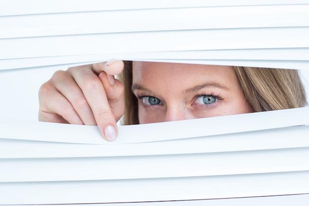 Mulher olhando através de persiana Foto Premium