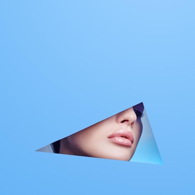 Mulher olhando no buraco, maquiagem linda e brilhante, olhos grandes e lábios, batom brilhante Foto Premium