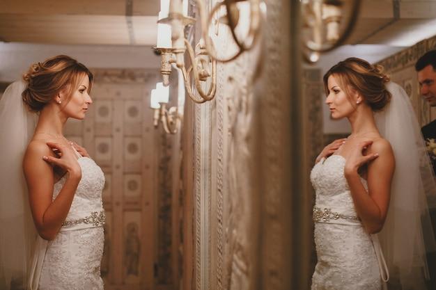 Mulher olhando o seu vestido de casamento no espelho Foto gratuita