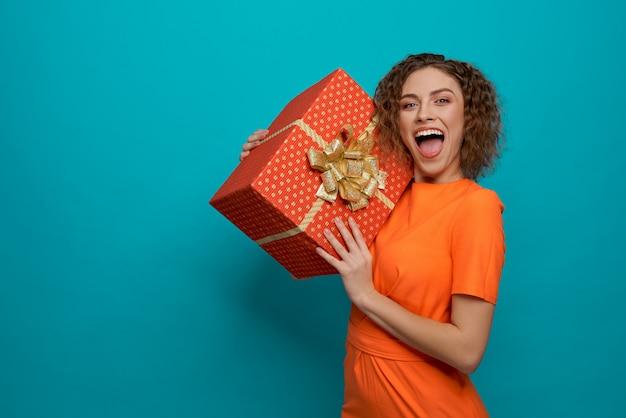 Mulher olhando para a câmera e gritando, mantendo presente Foto Premium